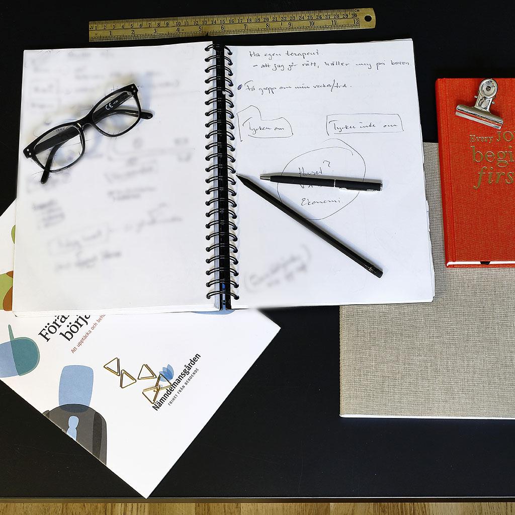 Ett uppslaget block med ett par glasögon på